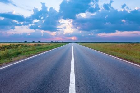 La carretera de asfalto hacia el sol naciente photo