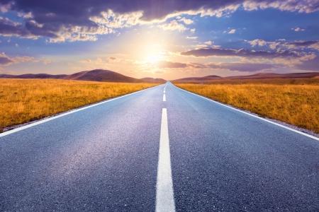 Zorgeloos rijden op een lege weg bij zonsondergang Stockfoto