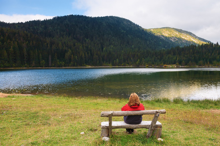 Lonely woman sits on a bench and watching the mountain Lake photo