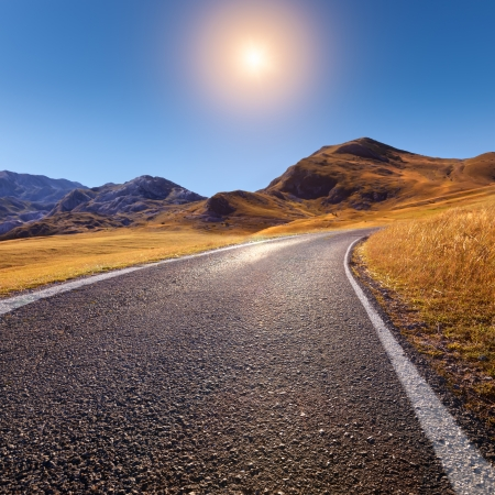 end of road: Driving on an empty mountain road to the sun Stock Photo