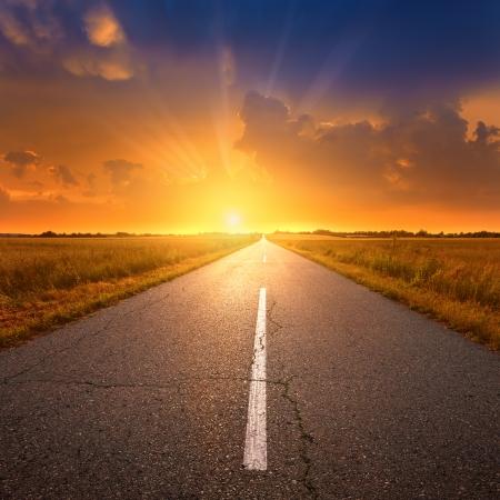 sunrise: Leere Asphaltstraße bei Sonnenuntergang