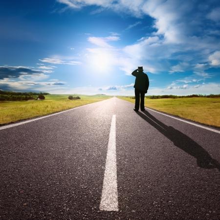 hombre solitario: Conducir en una carretera y solitario hombre vacío que está contra el sol