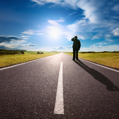 Driving on an empty road and lonely man who stands against\ the sun