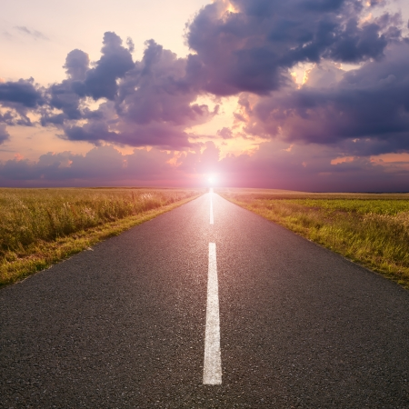 end of the line: Driving on an empty asphalt road to the rising sun