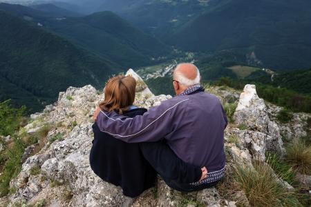 Senior couple enjoying the view from the top of the mountain photo