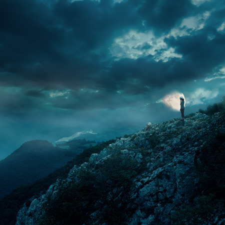 Young woman on the edge of the cliff during a full moon