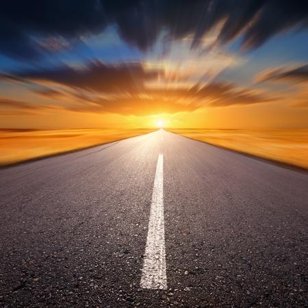 Blurred empty asphalt road at sunset photo
