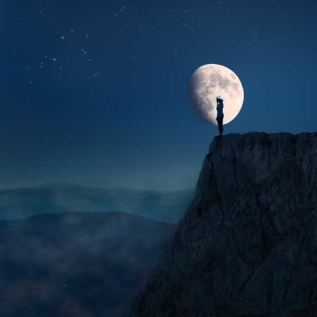 Young woman on edge of the cliff towards the moon Imagens