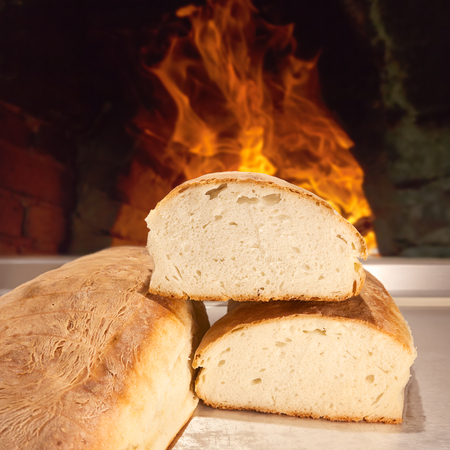Homemade bread just baked and removed from the furnace by wood chip photo