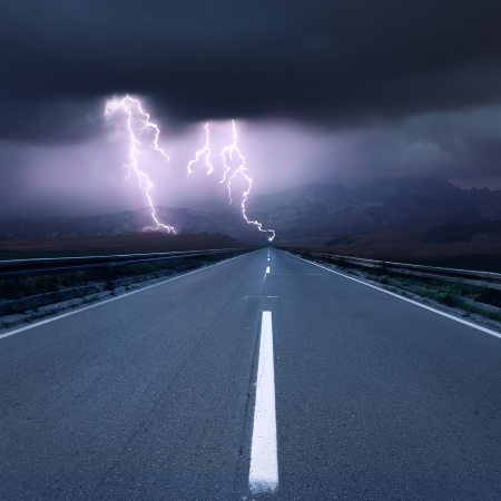 Driving on an empty asphalt road at thunderstorm
