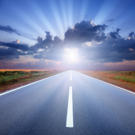 suns: Driving on an empty asphalt road to the suns rays