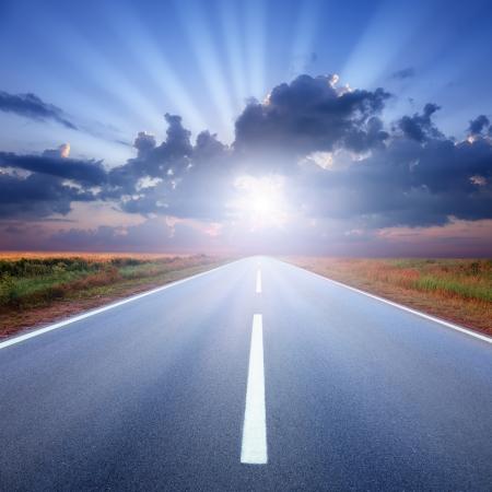 Rijden op een lege asfaltweg aan de stralen van de zon