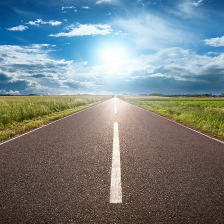 road ahead: Driving on an empty road towards the sun Stock Photo