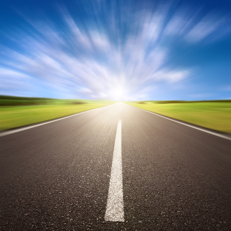 Driving on an blurred empty asphalt road at sunny day