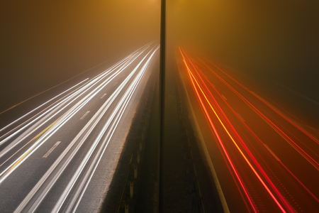 a highway with car light trails at misty night photo