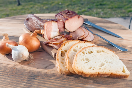 Smoked meat on wooden board with bread, onion and garlic photo