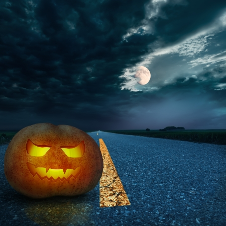 end of road: Jack O Lantern halloween pumpkin at night on the empty asphalt road