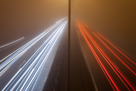 Long exposure photo on a highway with car light trails at misty night photo