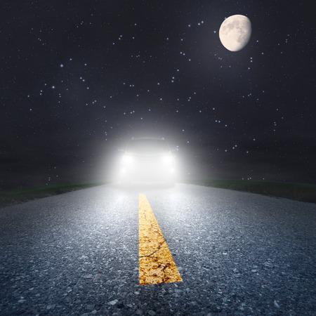 noche y luna: Conduciendo por una carretera asfaltada hacia los faros Foto de archivo