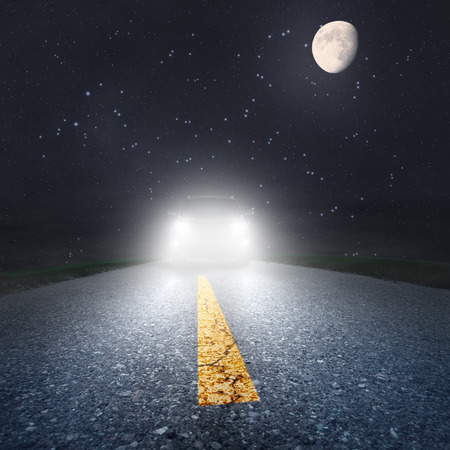 Driving on an asphalt road towards the headlights photo