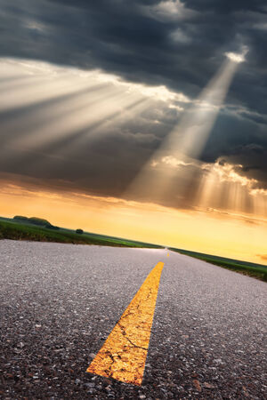 yelloow: Driving on an empty asphalt road to the suns rays