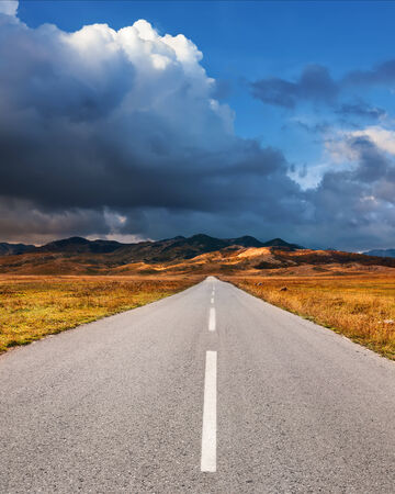 end of road: Driving on an empty asphalt road to the mountains at sunset Stock Photo