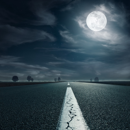 Driving on an empty asphalt road towards the full moon Banco de Imagens