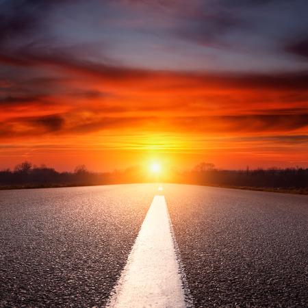 Driving on an empty asphalt road towards the setting sun