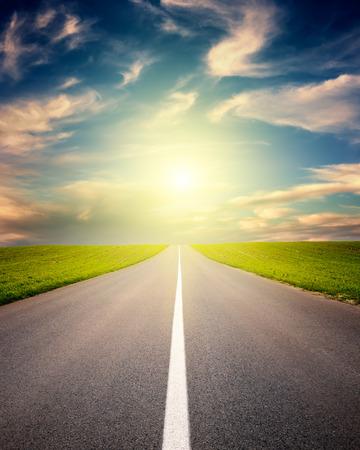 Rijden op een lege asfaltweg door het idyllische landschappen bij zonsondergang Stockfoto