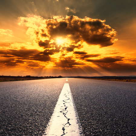 end of road: Driving on an empty asphalt road at sunset Stock Photo