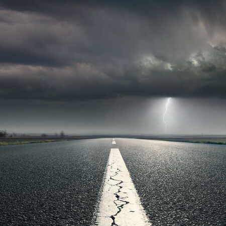 suspense: Driving on an empty road towards the lighting storm Stock Photo