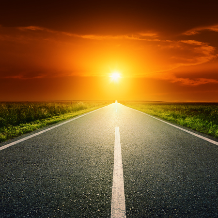 starting line: Driving on an empty asphalt road through the idyllic rural scenery at sunset