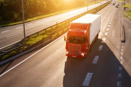 autobahn: Red truck in back light on the highway at sunny day