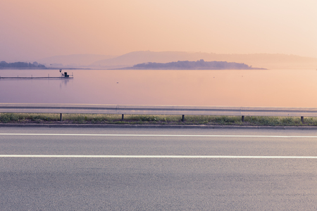the road surface: Side view of empty asphalt road and lake at sunrise