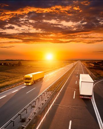 夕暮れ時に高速道路をトラック 2 台