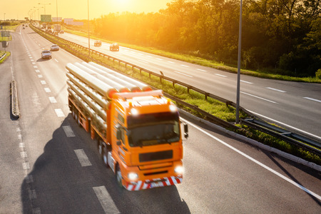 Orange LKW in Bewegungsunschärfe auf der Autobahn bei Sonnenuntergang Standard-Bild - 29298533