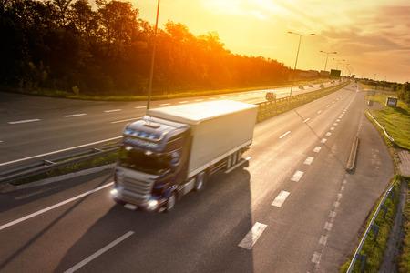 Blauwe vrachtwagen in motion blur op de snelweg bij zonsondergang