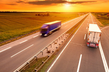 Blue and white truck in motion blur on the highway at sunset Stock Photo