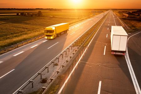 Gelbe und weiße LKW in Bewegungsunschärfe auf der Autobahn bei Sonnenuntergang Standard-Bild