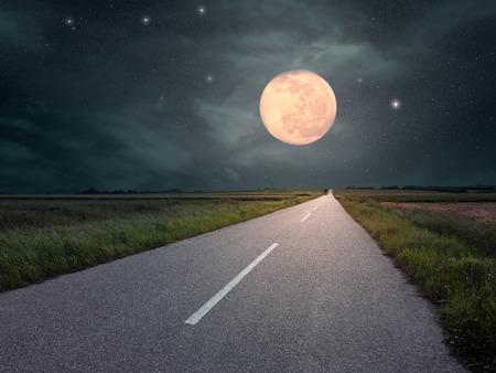 full moon romantic night: Driving on an empty asphalt road towards the full moon Stock Photo