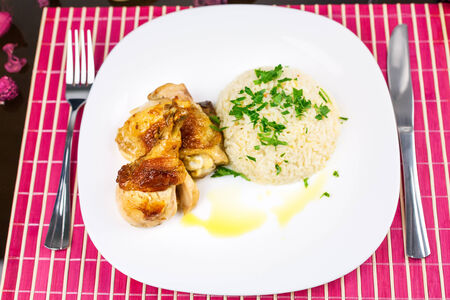 Roasted chicken drumsticks and rice on plate photo
