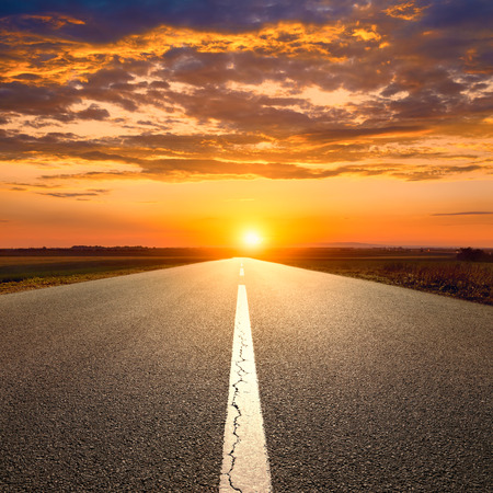 Driving on an empty asphalt road towards the sunset photo