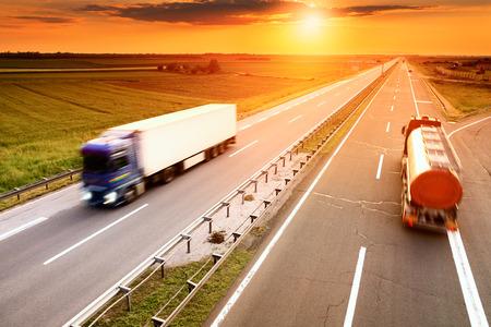 Dos camiones en el desenfoque de movimiento en la carretera al atardecer Foto de archivo - 30531917
