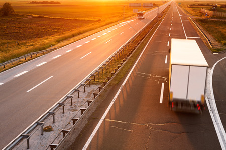 moving truck: Truck and bus on highway in motion blur at sunset Stock Photo