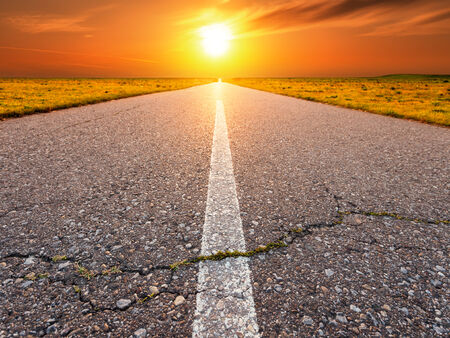 end of the line: Driving on an empty asphalt road towards the setting sun
