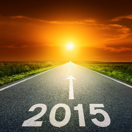 Driving on an empty road towards the setting sun to upcoming 2015