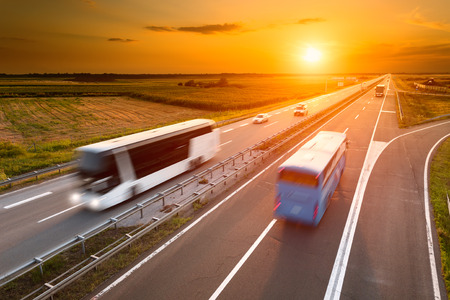 Two buses on highway in motion blur at sunset