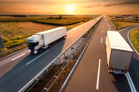 transporte de mercancia: Dos camiones en la carretera en el desenfoque de movimiento al atardecer Foto de archivo