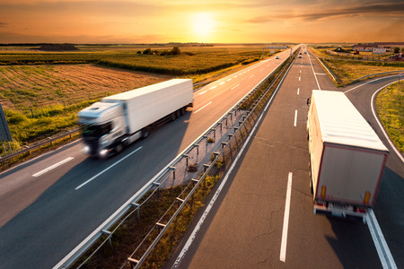 Two trucks on highway in motion blur at sunset Stockfoto