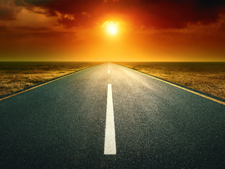 Driving on an empty road against the setting sun